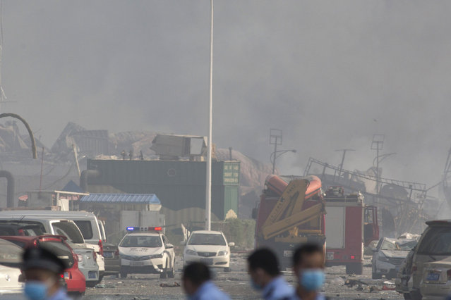 Chinese police officers work near the site of an explosion at a port in northeastern China's Tianjin municipality, Thursday, August 13, 2015. (Photo by Ng Han Guan/AP Photo)