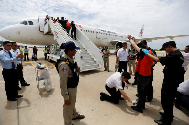 Chinese officials check the body of a suspect of telecom fraud as he is deported to China at the International Airport of Phnom Penh, Cambodia June 24, 2016. (Photo by Samrang Pring/Reuters)