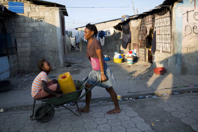 A girl carries her sister and and a jerry can of water in a wheelbarrow in Cite Soleil, a slum of Port-au-Prince, Haiti, Wednesday, January 29, 2020. (Photo by Dieu Nalio Chery/AP Photo)
