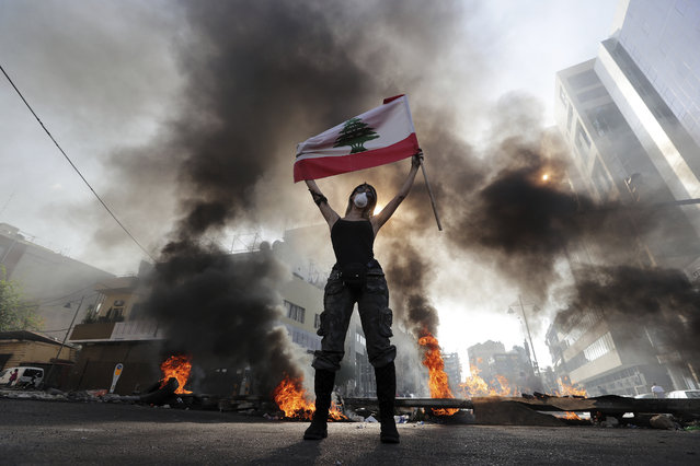 An anti-government protester holds a Lebanese flag while standing in front burning tires that block a road in the town of Jal el-Dib, north of Beirut, Lebanon, Wednesday, November 13, 2019. Lebanese protesters blocked major highways with burning tires and roadblocks on Wednesday, saying they will remain in the streets despite the president's appeal for them to go home. (Photo by Bilal Hussein/AP Photo)