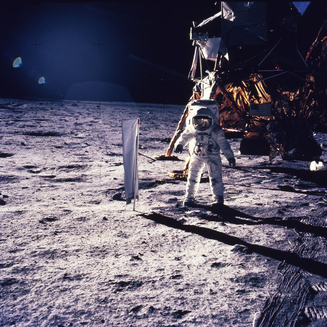 In this July 20, 1969 file photo provided by NASA, astronaut Edwin E. Aldrin Jr. walks on the surface of the moon, with seismogaphic equipment that he just set up. The flag like object on a pole is a solar wind experiment and in the background is the Lunar Landing Module. (Photo by AP Photo/NASA)