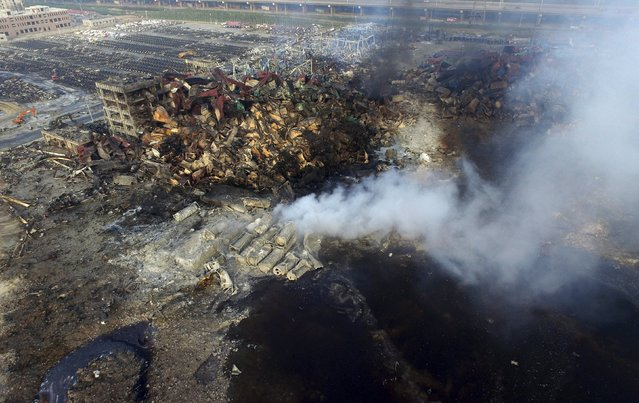 An aerial picture shows smoke rising from the debris among shipping containers at the site of Wednesday night's explosions at Binhai new district in Tianjin, China, August 15, 2015. (Photo by Reuters/Stringer)