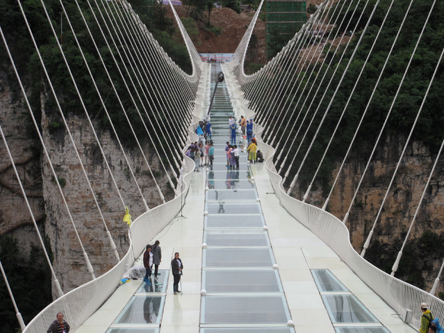People wait for a safety test ceremony of a 430-meter-long glass-bottom bridge in Zhangjiajie, Hunan province, China, June 25, 2016. (Photo by Jimmy Guan/Reuters)