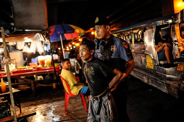 A suspected street robber is arrested by a policeman after a brief chase in the streets, June 20, 2016, in Manila, Philippines. (Photo by Dondi Tawatao/Getty Images)