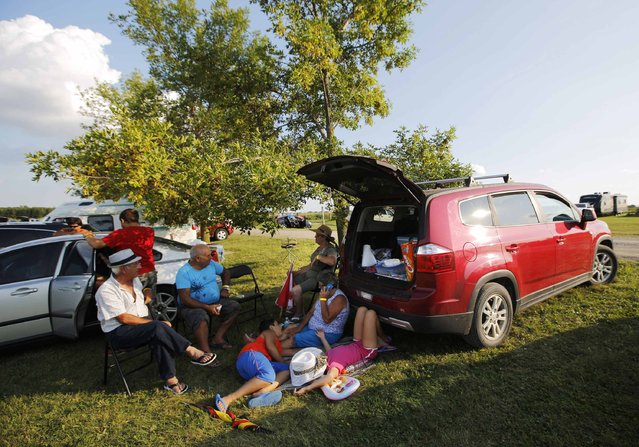 """Portuguese-Canadian family enjoys a tailgate party during the intermission at an Azorean """"tourada a corda"""" (bullfight by rope) in Brampton, Ontario August 15, 2015. (Photo by Chris Helgren/Reuters)"""