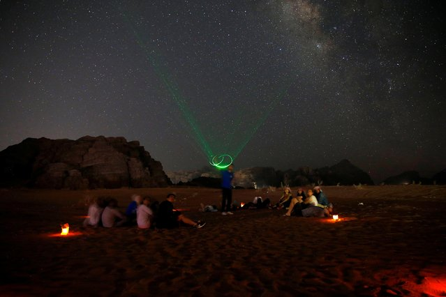 People look at the stars and planets over the Wadi Rum sky, south of Amman, Jordan, July 23, 2019. (Photo by Muhammad Hamed/Reuters)