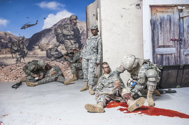 This is a combat life-saving course. Soldiers mimic serious injuries while recruits attempt to bandage them and get them out of the kill zone. (Photo and caption by Van Agtmael/Harrison Jacobs/Magnum Photos)