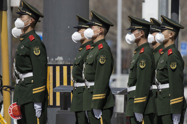Chinese paramilitary wearing masks form up during their duty in an embassy district in Beijing on Monday, March 16, 2020. With more imported cases of the new coronavirus, starting Monday, travelers arriving in Beijing from overseas will be quarantined for 14 days in designated facilities at their own expense. For most people, the new coronavirus causes only mild or moderate symptoms. For some it can cause more severe illness. (Photo by Ng Han Guan/AP Photo)