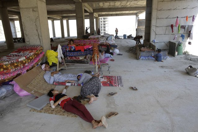 Displaced people from the minority Yazidi sect, who fled the violence in the Iraqi town of Sinjar, rest in an abandoned building they are using as their main residence outside the city of Dohuk August 14, 2014. Thousands of people, including members of the Yazidi religious minority, have fled to escape an advance by Sunni fighters from the Islamic State militant group. (Photo by Youssef Boudlal/Reuters)
