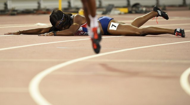Tiffany Porter of Great Britain lies on the track after taking a tumble at the finish line in the women's 100 metres hurdles final during the 15th IAAF World Championships at the National Stadium in Beijing, China August 28, 2015. (Photo by Dylan Martinez/Reuters)