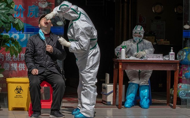 A medical worker wearing a full protective outfit tests a man for Covid-19 symptoms in a street in Wuhan, China, 01 April 2020. Wuhan, the epicenter of the coronavirus outbreak, partly lifted the lockdown allowing people to enter the city after more than two months. According to Chinese government figures over 2,500 people have died of Covid-19 in Wuhan since the outbreak began. (Photo by Roman Pilipey/EPA/EFE)