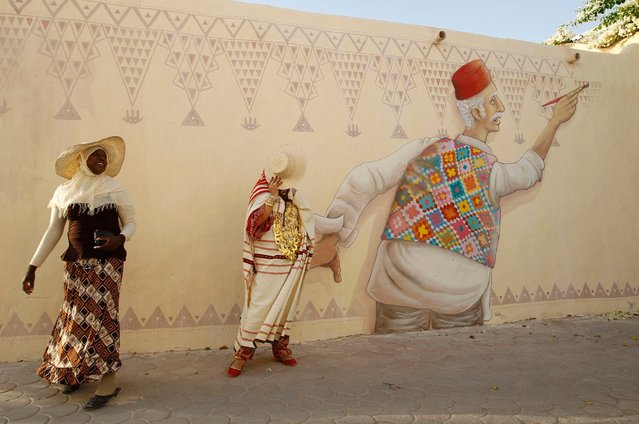 """Women walk next to a mural by Portuguese artist Mario Belem in the village of Erriadh on Djerba, also known as the """"Island of Dreams"""", on August 16, 2014. About a hundred artists from 30 countries arrived on Djerba to participate in the """"Djerba Hood"""" event, an open-air museum hosting the works of the artists. (Photo by Zoubeir Souissi/Reuters)"""