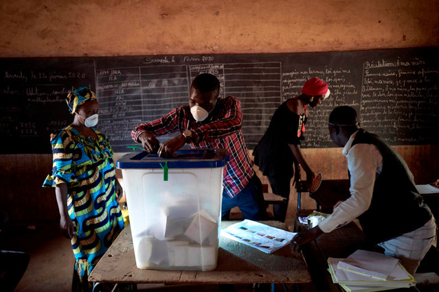 An electoral official wearing a mask as a preventive measure against the spread of the COVID-19 coronavirus removes the seals of a ballot box at a polling station in Bamako on March 29, 2020. Malians headed to the polls on March 29, 2020, for a long-delayed parliamentary election just hours after the country recorded its first COVID-19 coronavirus death and with the leading opposition figure kidnapped and believed to be in the hands of jihadists. (Photo by Michele Cattani/AFP Photo)