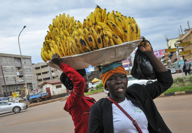 Women sell bananas in the street, after traders in markets were prohibited from selling any non-food items in an attempt to halt the spread of the new coronavirus, in Kampala, Uganda Thursday, March 26, 2020. (Photo by Ronald Kabuubi/AP Photo)