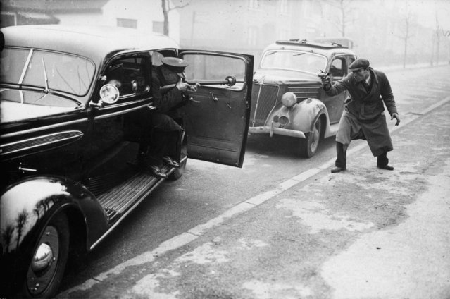 "A ""policeman"" and a ""gangster"" shoot it out in the streets of London during a demonstration of a new eight-cyclinder saloon car with bulletproof windows and pivot holes for guns. The car is being tested by officials at the Criminal Investigation Department of Scotland Yard. 15th January 1937. (Photo by J. A. Hampton/Topical Press Agency)"