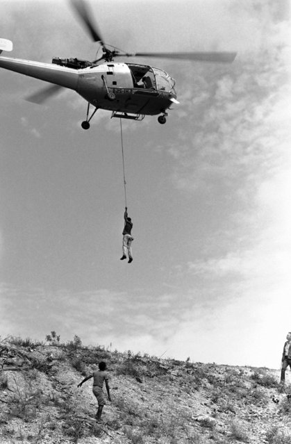 A Dominican helicopter lifts to safety a man who had been huddled in a small munitions dump on September 2, 1979 in Santo Domingo, Dominican Republic, since hurricane David struck at 5 p.m., on Friday. The dump was cut off by floodwaters. (Photo by Doug Jennings/AP Photo)