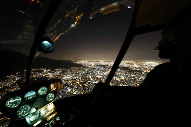 A pilot steers his helicopter at night over Rio de Janeiro, Brazil, less than two weeks before the start of the Rio 2016 Olympic Games, July 23, 2016. Picture taken July 23, 2016. (Photo by Pawel Kopczynski/Reuters)