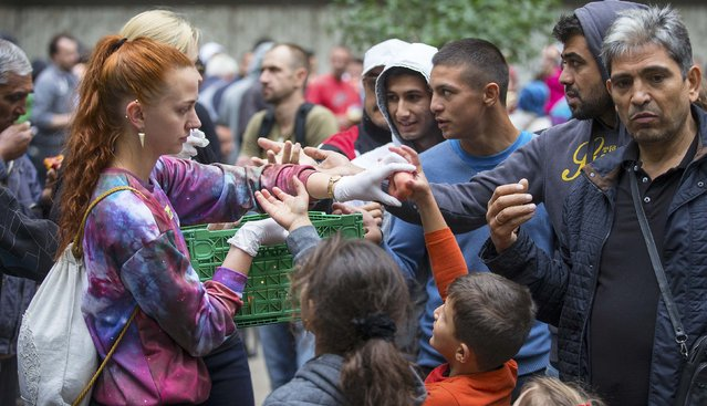 A helper distributes fruit to migrants in front of the State Office for Health and Social Affairs (LaGeSo), in Berlin, Germany, September 3, 2015. (Photo by Hannibal Hanschke/Reuters)