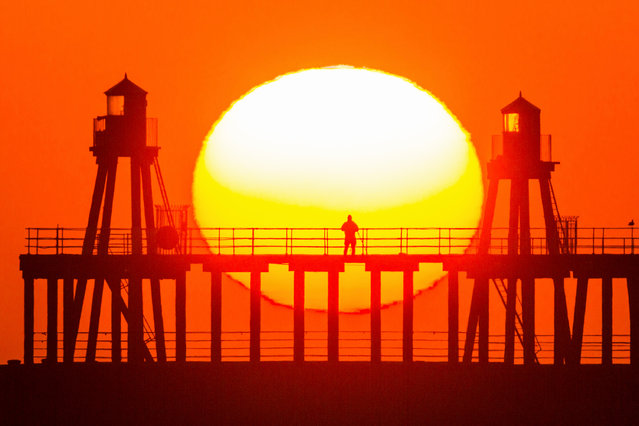 A man stands alone on the pier watching the sunrise on the North Yorkshire coast, England on March 23, 2020. (Photo by Andrew McCaren/LNP)