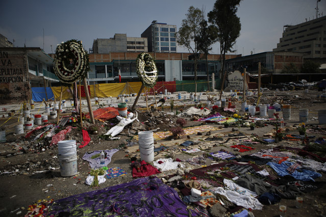 In this Monday, September 25, 2017 photo, flower wreaths, clothing, sewing supplies and a mannequin make up a memorial honoring those who died at 168 Bolivar Street when the five-story office and factory building was felled by an earthquake, in Mexico City. Businesses were located on four floors of offices at the building. Each business had no more than a half-dozen employees and there were likely no more than 50 people believed to be inside the building when the quake struck. (Photo by Rebecca Blackwell/AP Photo)