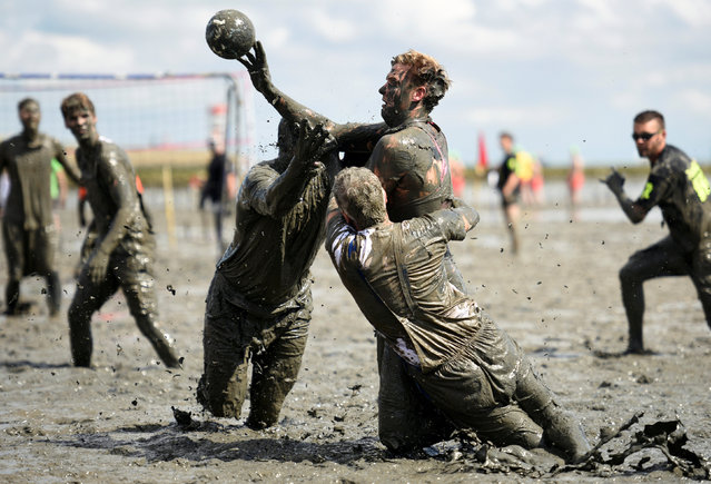 """Participants fight for the ball during a handball match at the so called """"Wattoluempiade"""" (Mud Olympics) in Brunsbuettel at the North Sea, Germany July 30, 2016.  REUTERS/Fabian Bimmer"""