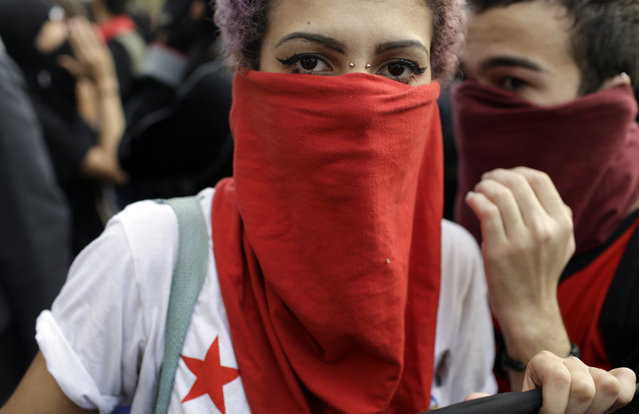 A demonstrator with her face covered marches during a protest on the route of the Olympic torch against the money spent on the Rio's 2016 Summer Olympics, in Niteroi, Brazil, Tuesday, August 2, 2016. The three-month torch relay across Brazil will end at the opening ceremony on Aug. 5, in Rio de Janeiro's Maracana stadium. (Photo by Leo Correa/AP Photo)