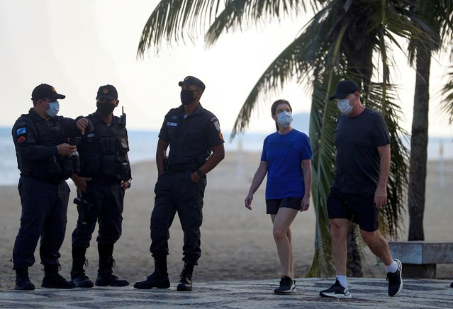A couple wearing protective masks walks next to police officers at the Ipanema beach, following the coronavirus disease (COVID-19) outbreak, in Rio de Janeiro, Brazil on May 17, 2020. (Photo by Pilar Olivares/Reuters)