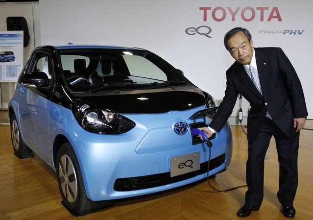 Toyota Motor Corp Vice Chairman Takeshi Uchiyamada puts a plug to the newly-developed compact electric vehicle eQ during a press conference in Tokyo, Japan, on September 25, 2012. Toyota is boosting its green vehicle lineup, with plans for 21 new hybrids in the next three years, a new electric car later this year and a fuel cell vehicle by 2015 in response to growing demand for fuel efficient and environmentally friendly driving. (Photo by Associated Press)