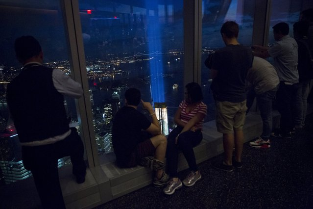 People peer through the windows at One World Observatory, the observation deck at One World Trade Center, as the Tribute in Light installation shines in Lower Manhattan in New York, September 11, 2015. (Photo by Andrew Kelly/Reuters)