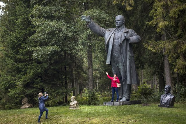 In this photo taken on Wednesday, October 4, 2017, visitors take photos near the statues of Soviet founder Vladimir Lenin at the Grutas Park, in Druskininkai, some 120 km (75 miles) south of the Lithuanian capital Vilnius, Lithuania. Grutas Park is a sculpture garden of Soviet-era statues and other Soviet ideological relics from the times of the Lithuanian SSR. (Photo by Mindaugas Kulbis/AP Photo)