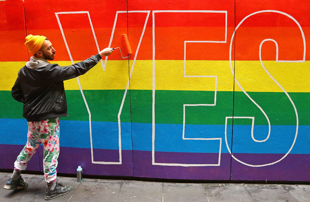 Artist David Pereirra paints a pro-gay marriage mural on a wall at Melbourne Central on August 27, 2017 in Melbourne, Australia. (Photo by Scott Barbour/Getty Images)