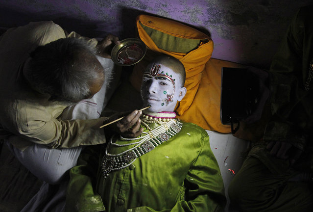 Amit Kumar, 14, a performer, gets makeup applied before performing the role of the Hindu lord Rama in a religious play ahead of Dussehra in the northern Indian city of Allahabad September 30, 2014. (Photo by Jitendra Prakash/Reuters)