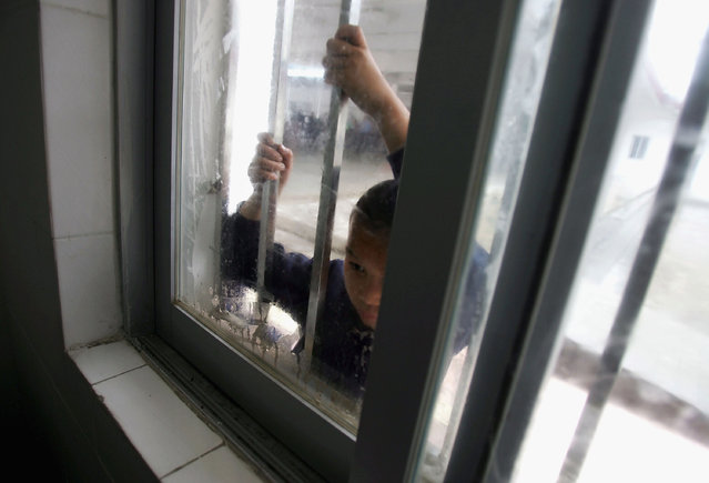 A kid looks into the infirmary through a window at an assistance center February 24, 2005 in Shenzhen, Guangdong Province, China. (Photo by Cancan Chu/Getty Images)