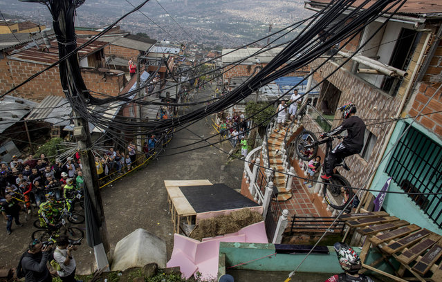 Residents watch as a downhill rider competes during the Urban Bike Inder Medellin race final at the Comuna 1 shantytown in Medellin, Antioquia department, Colombia on November 19, 2017. (Photo by Joaquin Sarmiento/AFP Photo)