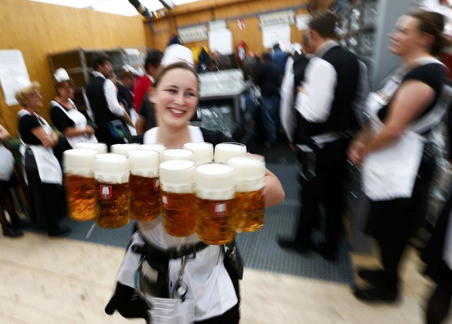 A waitress carries beer in a tent during the 182nd Oktoberfest in Munich, Germany, September 19, 2015. (Photo by Michaela Rehle/Reuters)