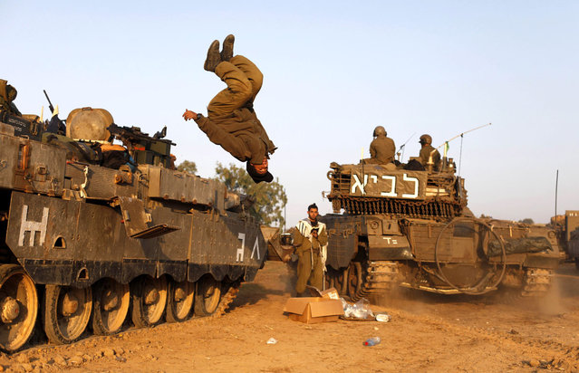 An Israeli soldier jumps from a tank in a deployment area as the conflict between Palestine and Gaza enters its seventh day on November 20, 2012 on Israel's border with the Gaza Strip. Hamas militants and Israel are continuing talks aimed at a ceasefire as the death toll in Gaza reaches over 100 with three Israelis also having been killed by rockets fired by Palestinian militants. (Photo by Lior Mizrahi)