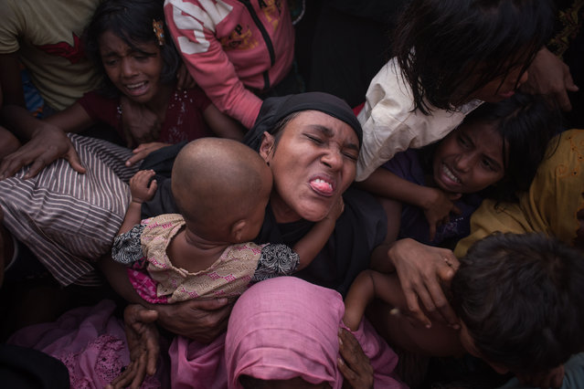 Rohingya Muslim refugees react as police and officials attempt to control a surging crowd as they wait to be called to recieve food aid of rice, water, and cooking oil in a relief centre at the Kutupalong refugee camp in Cox's Bazar on November 28, 2017. Rohingya are still fleeing into Bangladesh even after an agreement was signed with Myanmar to repatriate hundreds of thousands of the Muslim minority displaced along the border, officials said on November 27. (Photo by Ed Jones/AFP Photo)