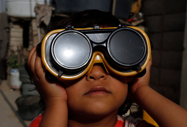 A child uses special protective glasses to observe a partial solar eclipse in Sanaa, Yemen, 21 June 2020. A partial solar eclipse occurs when a portion of the Earth is engulfed by the shadow (penumbra) cast by the Moon as it passes between our planet and the Sun in imperfect alignment. (Photo by Yahya Arhab/EPA/EFE)