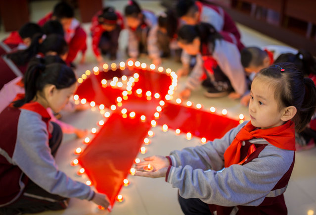 Students use candles to form a large ribbon during an event to mark World AIDS Day at a primary school in Hohhot, Inner Mongolia autonomous region, China December 1, 2017. (Photo by Reuters/China Stringer Network)