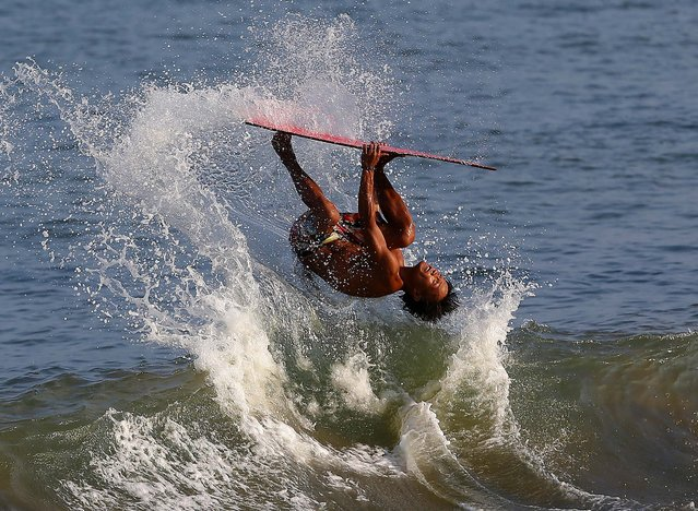 Rioben Vivero does a backflip on his skimboard at the shoreline of the coastal town of Tanauan, Leyte province, central Philippines on Sunday, October 12, 2014. Skimboarding is gaining popularity in this coastal town that was badly hit by Typhoon Haiyan last year. (Photo by Aaron Favila/AP Photo)