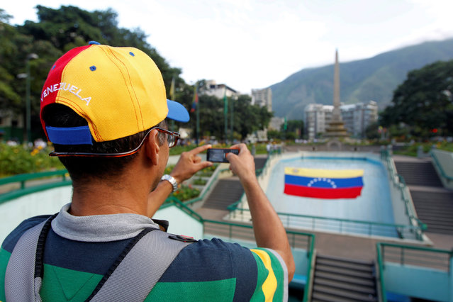 An opposition supporter wearing a cap with the colours of the national flag, takes a photo with his cell phone during a rally to demand a referendum to remove Venezuela's President Nicolas Maduro in Caracas, Venezuela, September 1, 2016. (Photo by Christian Veron/Reuters)