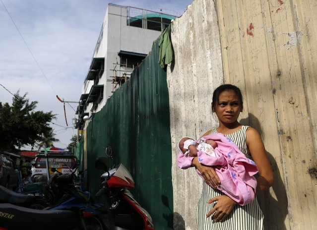 A Filipino mother holding her baby stands at the wall of a jail in Paranaque city, south of Manila, Philippines, 12 August 2016. A lockdown is in place at a jail after a bombing incident occurred that resulted in the deaths of detainees. At least 10 inmates have died after an explosion rocked the Paranaque City Jail on the evening of 11 August, according to Paranaque Mayor Edwin Olivarez. Two Chinese detainees were among the dead. Paranaque Deputy Chief of Police Superintendent Wilson Doromal said in a statement that the inmates wanted to discuss the issue on the transfer of detention cells, an explosion ensued while a meeting was held inside the office of the jail warden. (Photo by Francis R. Malasig/EPA)