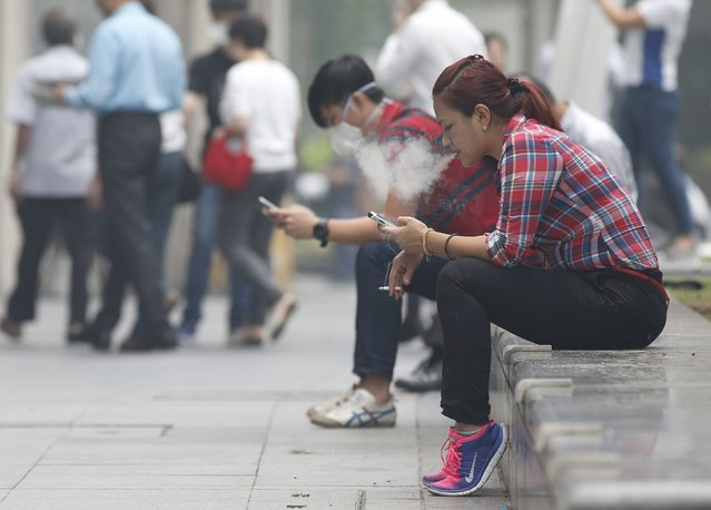 A woman smokes a cigarette next to man wearing a mask during lunch hour at the central business district in Singapore September 29, 2015. (Photo by Edgar Su/Reuters)