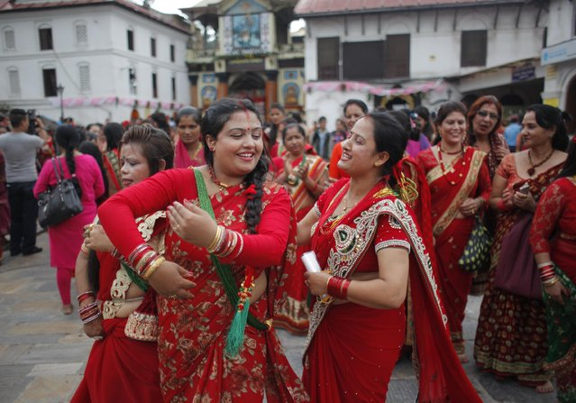 Nepalese Hindu women dance during Teej festival at the Pashupatinath Hindu Temple in Kathmandu, Nepal, Sunday, September 4, 2016. During this festival, married Hindu women observe day-long fast and pray for a happy married life while those unmarried pray for a good husband. (Photo by Niranjan Shrestha/AP Photo)