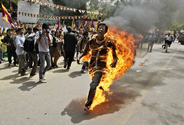 In this March 26, 2012 file photo, Tibetan exile Jamphel Yeshi screams as he runs engulfed in flames after setting himself on fire at a protest in New Delhi, India, against Chinese President Hu Jintao's visit to India. Yeshi died Wednesday, March 28, 2012. (Photo by Manish Swarup/AP Photo)