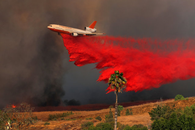 A DC-10 aircraft drops fire retardant on a wind-driven wildfire in Orange, California, U.S., October 9, 2017. (Photo by Mike Blake/Reuters)