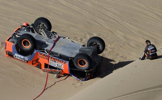 Driver Robby Gordon of the U.S. looks at his overturned Hummer during the 4th stage of the 2013 Dakar Rally. (Photo by Franck Fife/Associated Press)