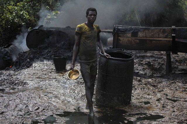 A crude oil refinery worker stands in front of a locally made burner in an illegal oil refinery site near river Nun in Nigeria's oil state of Bayelsa, November 27, 2012. The worker said that he had been doing the job for two years and earned the equivalent of around $60 a day. (Photo by Akintunde Akinleye/Reuters)