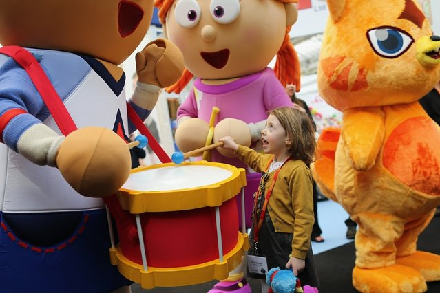 Betsy McCredie, 4, from Glasgow interacts with life size cartoon characters during the 2013 London Toy Fair at Olympia Exhibition Centre on January 22, 2013 in London, England. The annual fair which is organised by the British Toy and Hobby Association, brings together toy manufacturers and retailers from around the world.  (Photo by Dan Kitwood)