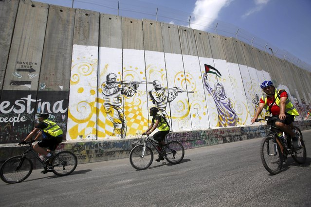 Cyclists ride their bicycles past a section of the Israeli barrier during a cycling challenge in the occupied West Bank city of Bethlehem October 2, 2015. (Photo by Mussa Qawasma/Reuters)